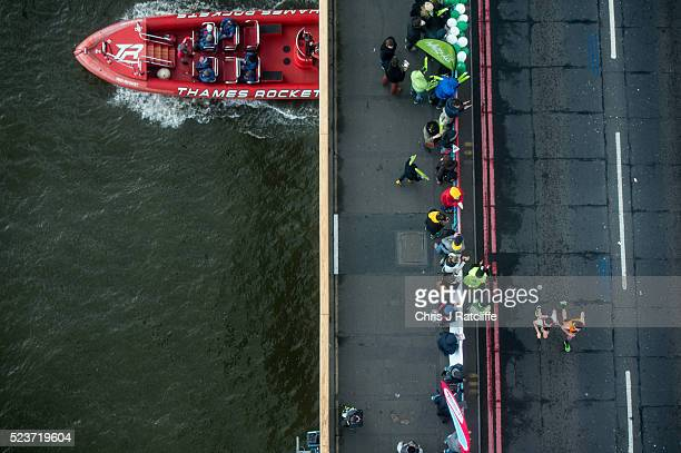 A visually impaired runner and his companion cross over Tower Bridge as seen from the glass floor of Tower Bridge walkway during the 36th London...