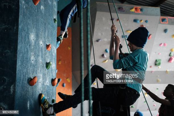 A visually impaired student challenges rope climbing during a weeklong free climbing training for visually impaired and blind students by the...