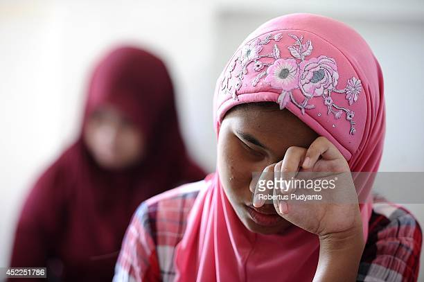 A visually impaired student falls a sleep during Ramadan class at The Foundation for The Education of Blind Children on July 17 2014 in Surabaya...