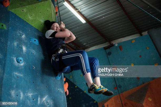 A visually impaired student smiles as she finishes rope climbing during a weeklong free climbing training for visually impaired and blind students by...