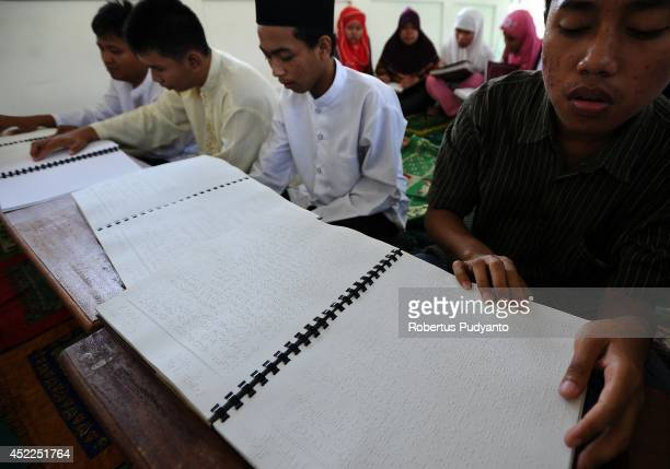Visually impaired students read a Braille Quran at The Foundation for The Education of Blind Children during Ramadan on July 17 2014 in Surabaya...