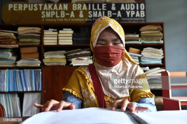 Visually impaired teacher reads a Braille book during World Braille Day on January 04, 2021 in Surabaya, Indonesia. World Braille Day 2021, which is...