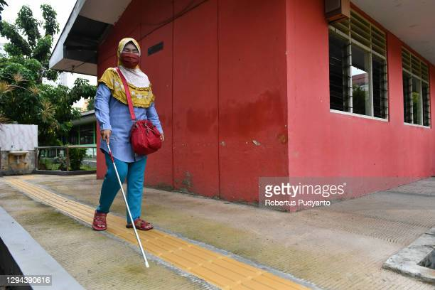 Visually impaired teacher walks to school during World Braille Day on January 04, 2021 in Surabaya, Indonesia. World Braille Day 2021, which is...