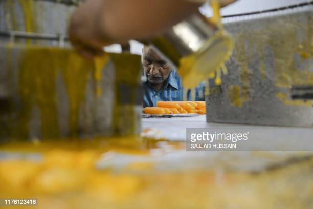 A visually impaired worker makes candles in a workshop of the Blind School Relief Association in New Delhi on October 16 2019 The association sells...
