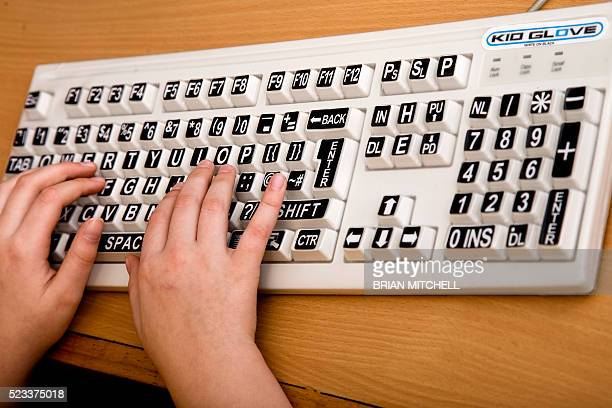 visually impared childl using specially large key computer key pad - assistive technology stock pictures, royalty-free photos & images