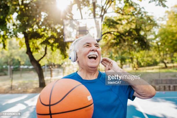 バスケットボールフィールドのバイタルで幸せなシニアマン - court hearing ストックフォトと画像