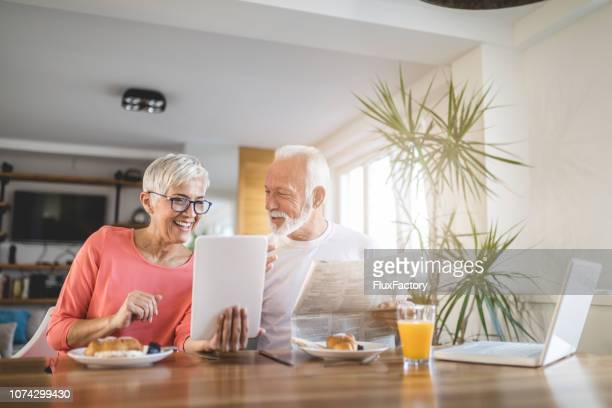 vital senior couple enjoying their time during breakfast - publication stock pictures, royalty-free photos & images