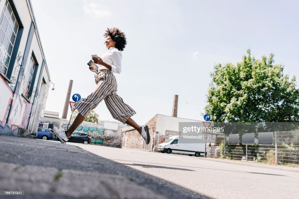 Vital young woman crossing the street : Stock Photo