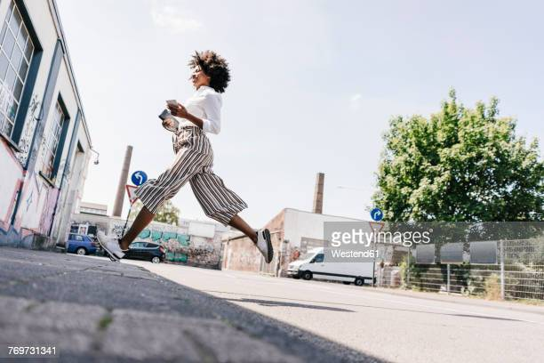 vital young woman crossing the street - black trousers stock pictures, royalty-free photos & images