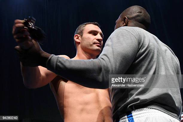 Vitali Klitschko of Ukraine takes off the sunglasses of Kevin Johnson of USA during the weigh in at the Postfinance-Arena on December 11, 2009 in...