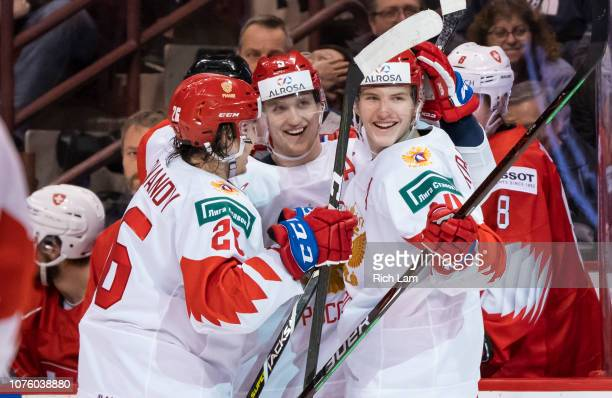 Vitali Kravtsov of Russia celebrates with teammates Dmitri Samorukov and Alexander Romanov after scoring a goal against Switzerland in Group A hockey...