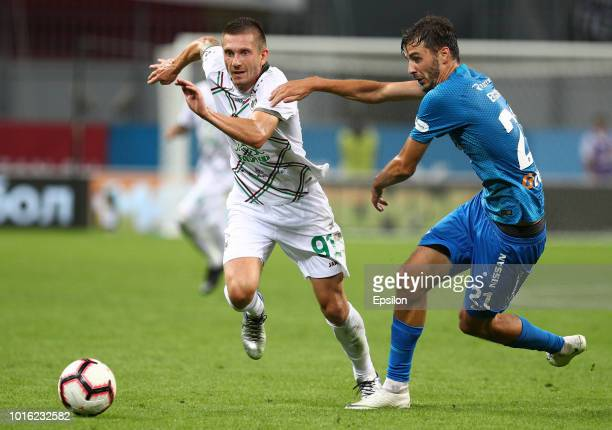 Vitali Ustinov of FC Rubin Kazan vies for the ball with Aleksandr Yerokhin FC Zenit Saint Petersburg during the Russian Premier League match between...