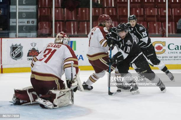 Vitalii Abramov of the Gatineau Olympiques fires the puck against Louis-Philip Fortin of the Acadie-Bathurst Titan as Reilly Pickard guards his net...