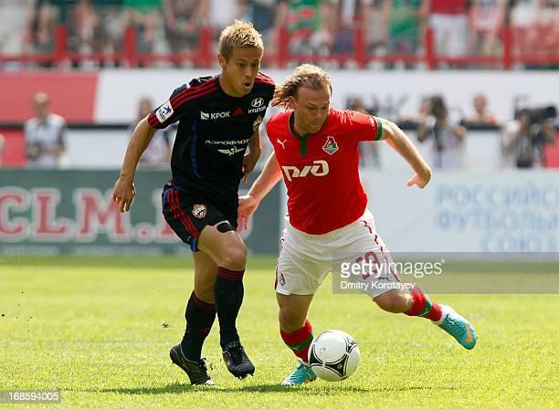 Vitaliy Denisov of FC Lokomotiv Moscow is challenged by Keisuke Honda of PFC CSKA Moscow during the Russian Premier League match between FC Lokomotiv...