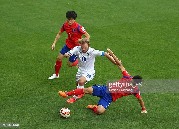 Vitaliy Denisov of Uzbekistan is challenged by Lee Keun Ho and Kim Changsoo of Korea Republic during the 2015 Asian Cup match between Korea Republic...