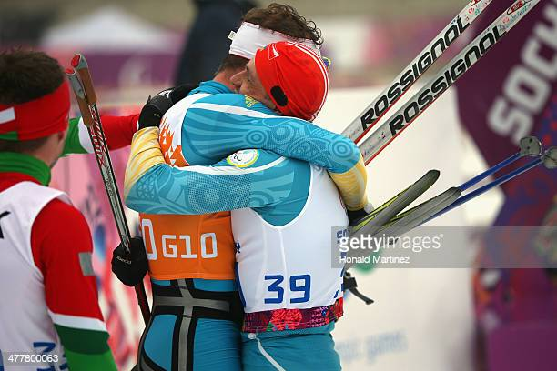 Vitaliy Lukyanenko of Ukraine and guide Borys Babar embrace after winning the gold medal in Men's 125km Visually Impaired Biathlon during day four of...