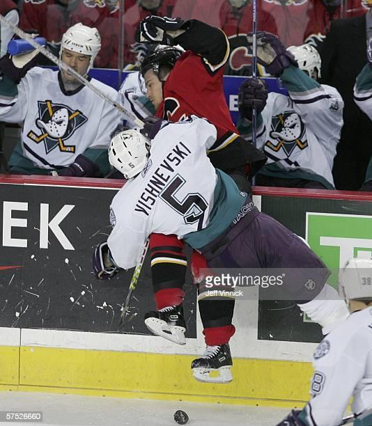 Vitaly Vishnevski of the Anaheim Mighty Ducks checks Andrew Ference of the Calgary Flames along the Mighty Ducks bench in game seven of the Western...
