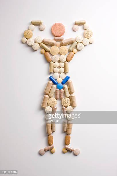 Vitamin pills in shape of man flexing muscles