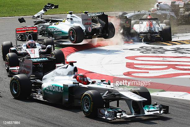 Vitantonio Liuzzi of Italy and Hispania Racing Team loses control of his car and crashes into Nico Rosberg of Germany and Mercedes GP at the start of...