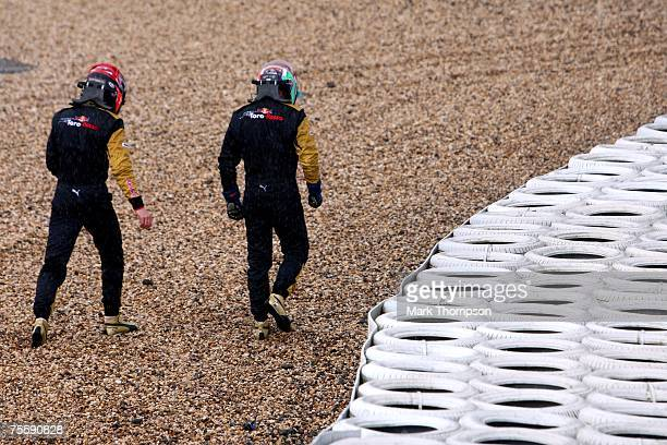 Vitantonio Liuzzi of Italy and Scuderia Toro Rosso and Scott Speed of United States and Scuderia Toro Rosso walk from the track after sliding out...