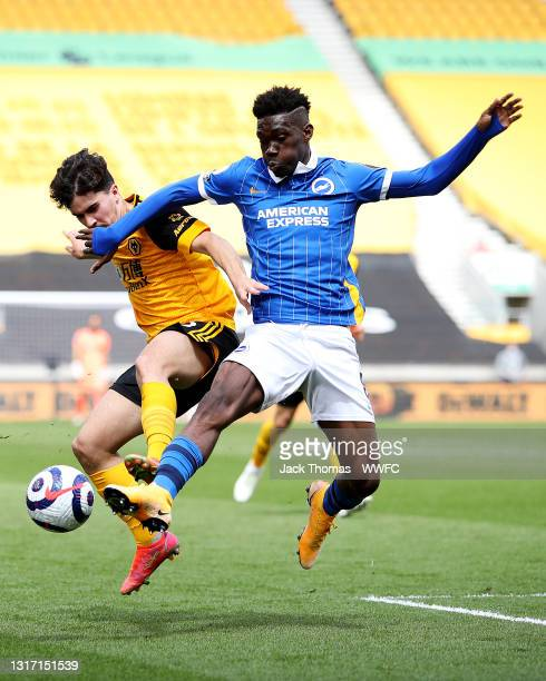 Vitinha of Wolverhampton Wanderers is challenged by Yves Bissouma of Brighton & Hove Albion during the Premier League match between Wolverhampton...