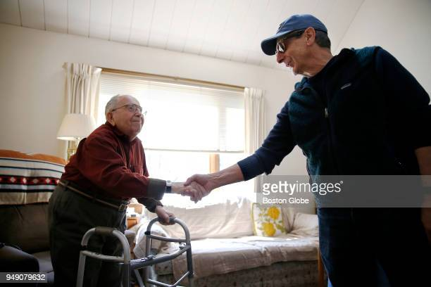 Vito LaMura right shakes hands with Joseph Ballota as he makes a Meals on Wheels delivery to the Ballotas' home in Lexington MA on March 27 2018 The...