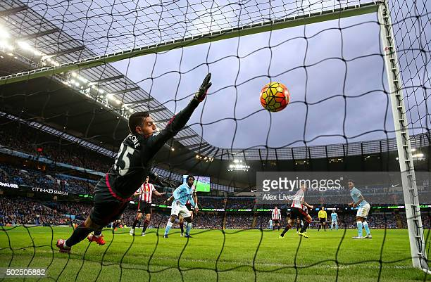 Vito Mannone of Sunderland dives in vain as Raheem Sterling of Manchester City scores the opening goal during the Barclays Premier League match...
