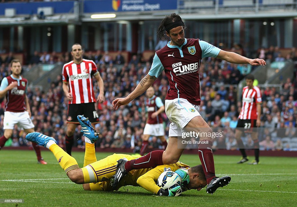 Vito Mannone of Sunderland dives to make a save at the feet of George Boyd of Burnley during the Barclays Premier League match between Burnley and Sunderland at Turf Moor on September 20, 2014 in Burnley, England.