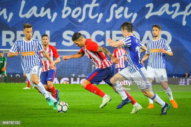 Vitolo of Atletico Madrid duels for the ball with Sergio Canales and Aritz Elustondo of Real Sociedad during the Spanish league football match...