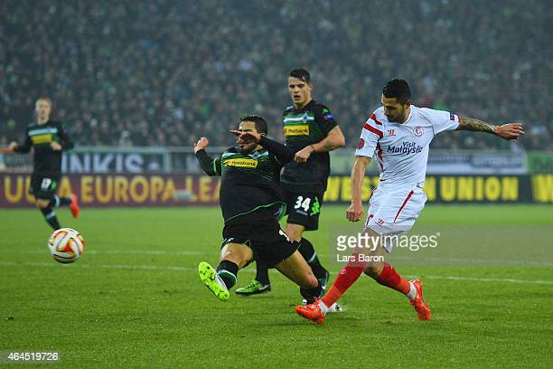 Vitolo of Sevilla shoots past Alvaro Dominguez of Borussia Moenchengladbach to score their second goal during the UEFA Europa League Round of 32...