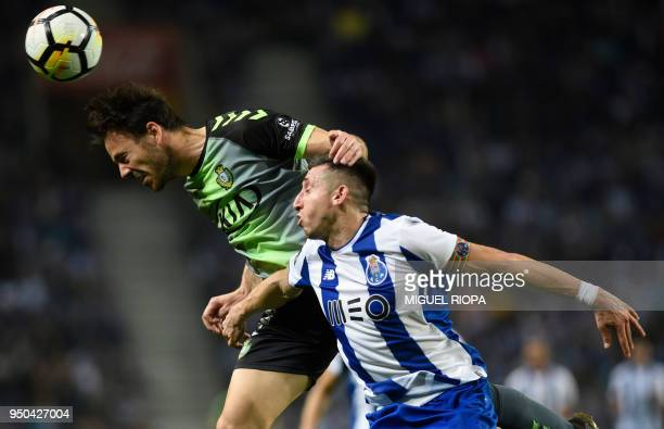 Vitoria FC's Portuguese defender Yohan Tavares heads the ball next to Porto's Mexican midfielder Hector Herrera during the Portuguese league football...