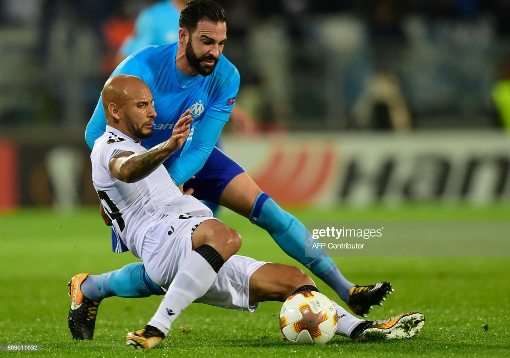 Vitoria Guimaraes' Brazilian forward Rafael Martins (front) challenges Marseille's French defender Adil Rami during the UEFA Europa League group I football match Vitoria SC vs Marseille at the D. Afonso Henriques stadium in Guimaraes on November 2, 2017. /
