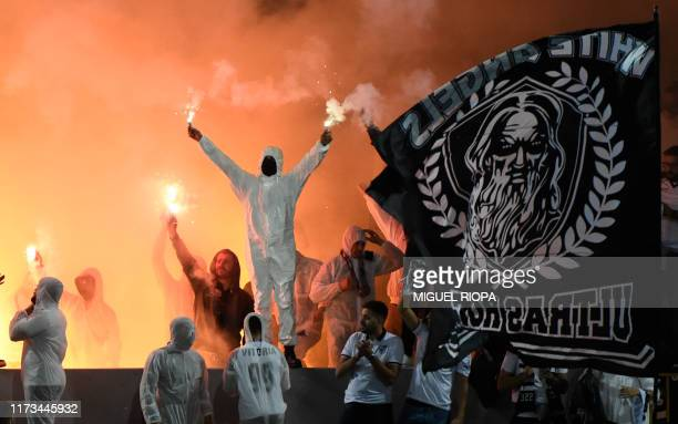Vitoria Guimaraes' supporters light flares before the start of the UEFA Europa League group F football match between Vitoria Guimaraes and Eintracht...