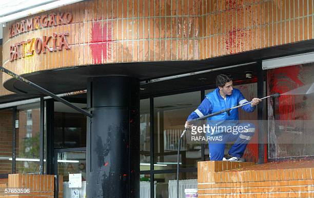 "Cleaning company worker removes paint from the windows of a ""batzoki"" in the northern Spanish Basque city of Vitoria, after it was attacked, 19 May..."