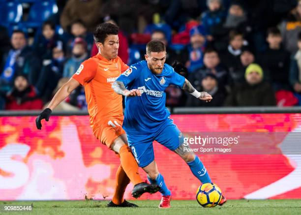 Vitorino Gabriel Pacheco Antunes of Getafe CF fights for the ball with Adalberto Penaranda of Malaga CF during the La Liga 201718 match between...