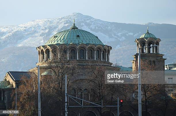 Vitosha Mountain looms behind St Nedelya Eastern Orthodox church on December 8 2013 in Sofia Bulgaria Sofia is becoming an increasingly popular...