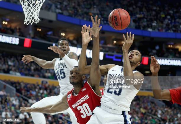 Vitto Brown of the Wisconsin Badgers and Mikal Bridges of the Villanova Wildcats battle for a loose ball during the second round of the 2017 NCAA...