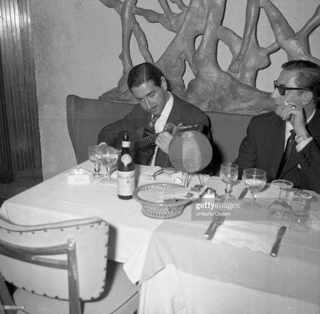 Vittorio de Sica (right) is with Jaime de Mora y Aragón (left) in an Italian restaurant while Jaime plays the guitar, Italy 1961.