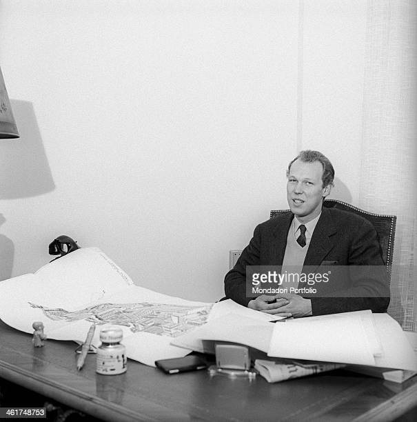 Vittorio Emanuele of Savoy son of the last king of Italy being interviewed at his workplace with the desktop full of land registry maps and floor...