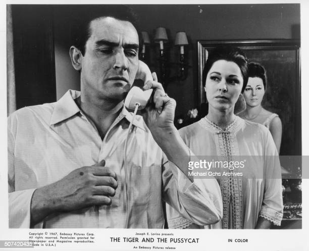 Vittorio Gassman listens on the phone as Antonella Steni looks on in a scene from the movie The Tiger and the Pussycat circa 1967