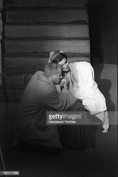 Vittorio Gassman on his knees in front of Ilaria Occhini who is sat down he is taking her hand in a scene of the play 'Un marziano a Roma' Teatro...