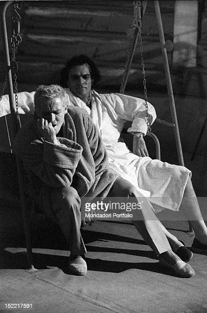 Vittorio Gassman wearing a dressing gown and sat down on a lawn swing with the actor Franco Giacobini in a scene of the play 'Un marziano a Roma'...