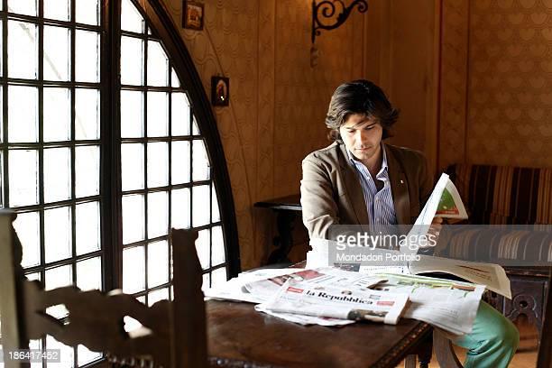 Vittorio Sgarbi's son Carlo Sgarbi Brenner reading the newspaper La Repubblica seated in a room of Villa Banfi. Vimercate, 2000s.
