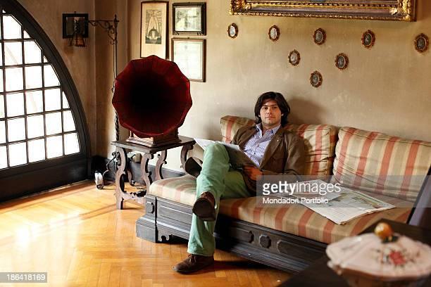 Vittorio Sgarbi's son Carlo Sgarbi Brenner sitting on the sofa in the livingroom of Villa Banfi. Vimercate, 2000s.