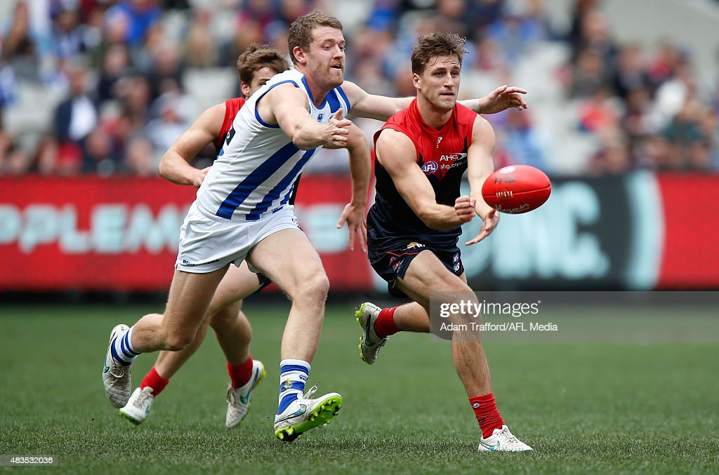 Viv Michie of the Demons is tackled by Lachlan Hansen of the Kangaroos during the 2015 AFL round 19 match between the Melbourne Demons and the North Melbourne Kangaroos at the Melbourne Cricket Ground, Melbourne, Australia on August 9, 2015.