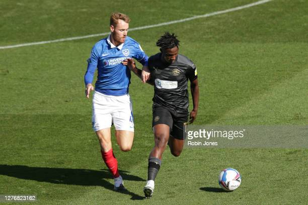 Viv Solomon-Otabor of Wigan Athletic holds off Tom Naylor of Portsmouth FC during the Sky Bet League One match between Portsmouth and Wigan Athletic...