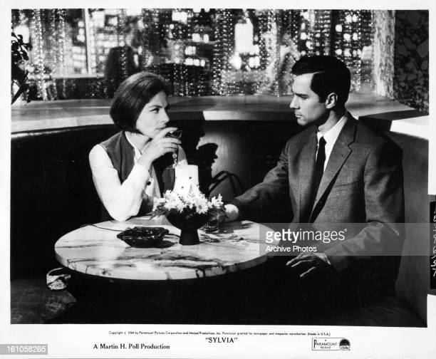 Viveca Lindfors and George Maharis having drink in scene from the film 'Sylvia' 1965