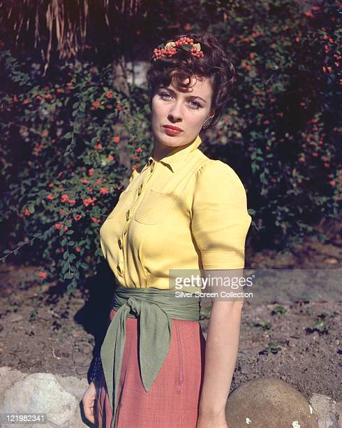 Viveca Lindfors Swedish actress wearing a yellow shortsleeved blouse and a pink skirt with a green wrap belt posing in front of bushes bearing red...
