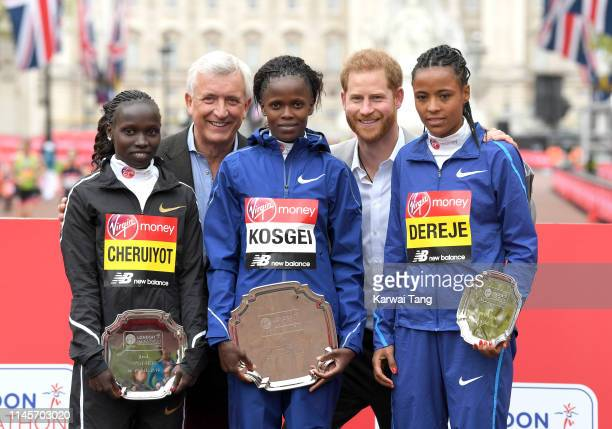 Vivian Cheruiyot of Kenya Brigid Kosgei of Kenya and Roza Dereje of Ethiopia pose with Prince Harry Duke of Sussex on the podium after competing in...