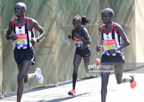 Vivian Cheruiyot of Kenya runs with her pacemakers at the halfway point during the Virgin London Marathon on April 22 2018 in London Cheruiyot won...